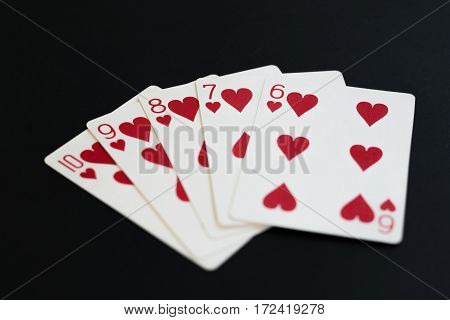 Straight Flush of hearts in poker cards game on a black background.