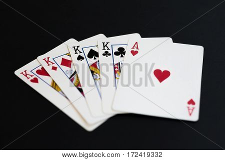 Four of a kind in poker cards game on a black background.