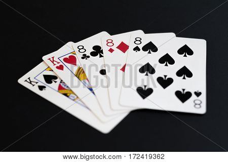 Full house in poker cards game on a black background.