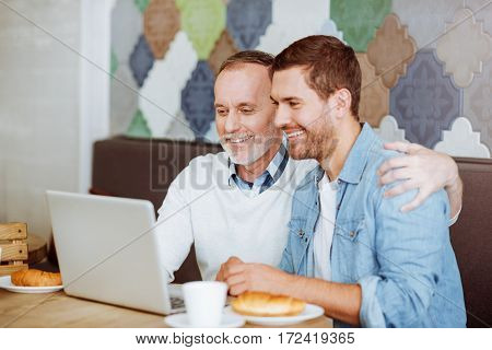 Internet communication. Positive deligyted aged man and his grandson sitting at the table and using laptop while restin together in the cafe