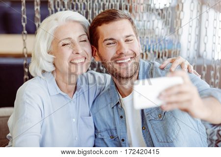 Only positive emotions. Cheerful content aged woman and her grandson sitting at the table and making selfies while resitng in the cafe