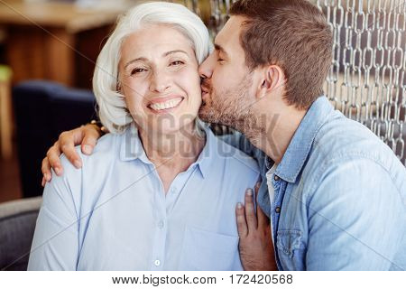 With love. Cheerful loving man kissing her grandmother and expressing positive emotions while sitting in the cafe