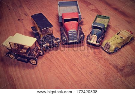 Vintage toy cars (lorry (truck) and convertible car) on brown wooden background. Retro toys for boys. Flat design with blank and free space. Retro effect.