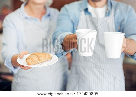 THats for you. Pleasant waiters holding coffee and freshly made baking while welcoming guests