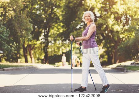 Staying healthy. Nice positive elderly woman holding poles and walking while doing sports activities in the park