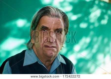Real senior Cuban people and emotions portrait of sad old latino looking at camera. Depressed hispanic elderly man from Havana Cuba