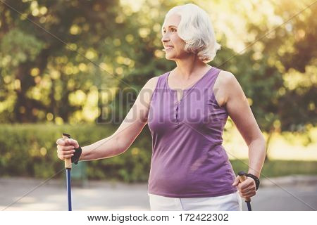 Sports equipment. Cheerful grey haired senior woman holding walking poles and smiling while enjoying her time in the park