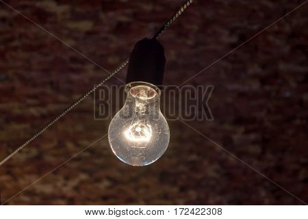 Light bulb hanging on a electric cable in front of a brick wall