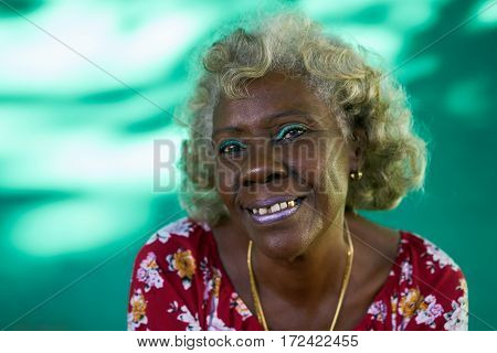 Old hispanic real people from Cuba with feelings and emotions portrait of bizarre senior african american lady smiling laughing and looking at camera.