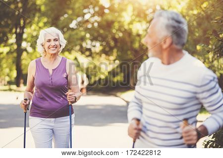 Sports activities. Joyful delighted aged woman holding the walking poles and looking at her husband while going after him