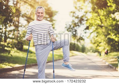 Pleasant activity. Joyful nice aged man holding walking poles and exercising while practicing Nordic walking