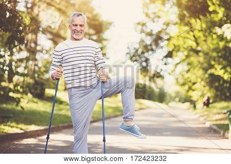 Pleasant activity. Joyful nice aged man holding walking poles and exercising while practicing Nordic walking
