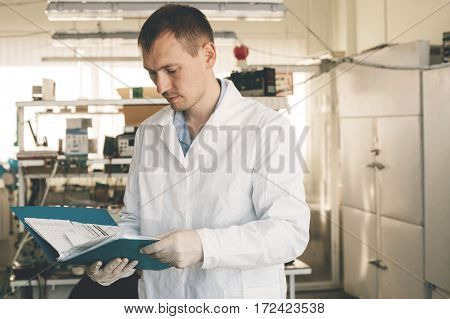 A man in a white coat examines the startup project. Start your own business in a small workplace.