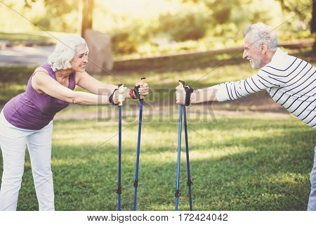 Physical activity. Happy positive elderly couple holding walking poles and leaning forwards while standing opposite each other