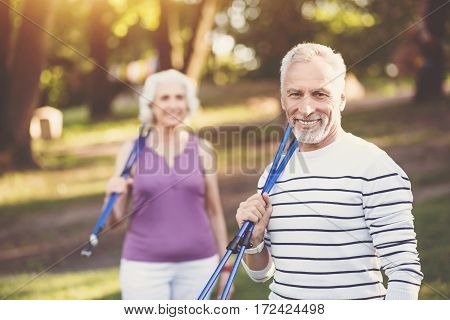Exercising outdoors. Cheerful handsome senior man smiling and holding walking poles on his shoulder while looking at you