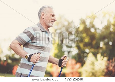I love sport. Cheerful delighted elderly man smiling and doing some sports activities while being outside