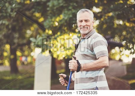 Age is nothing. Pleasant senior positive man smiling and looking at you while standing with poles in the park