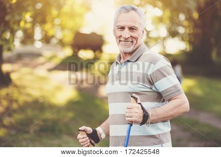 Sport walking. Delighted well built aged man smiling and enjoying his walk while being in the park