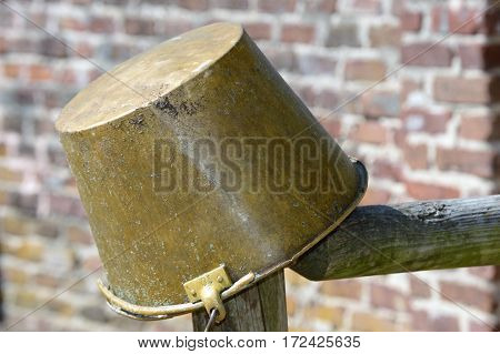 galvanized horse feed bucket on wooden fence post