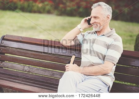 Pleasant conversation. Delighted positive good looking man sitting on the bench and putting his cell phone to the ear while having an interesting conversation