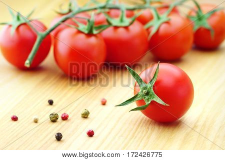 Fresh cherry tomatoes on the wooden background.