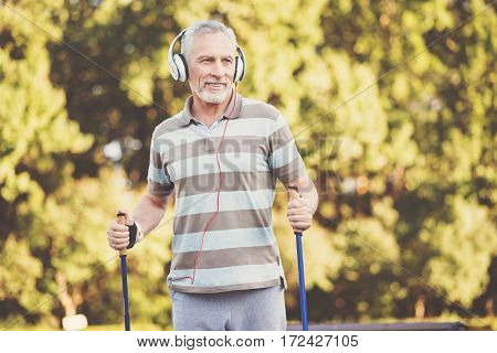 Listening to music. Nice aged positive man wearing headphones and listening to music while practicing Nordic walking
