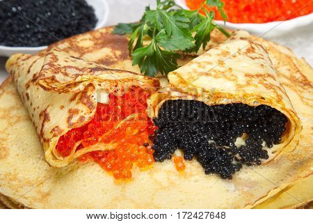 Pancakes with red and black caviar. Caviar wrapped in pancakes.