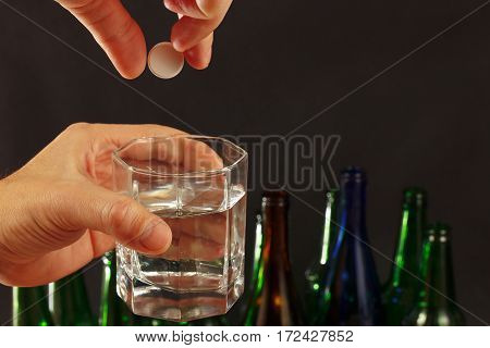 Hand with an effervescent tablet from hangover over a glass of water on a dark background.