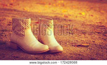 Outdoor footwear fashion concept. Shoes standing on ground. Pair of boots outside surrounded by dried leaves.