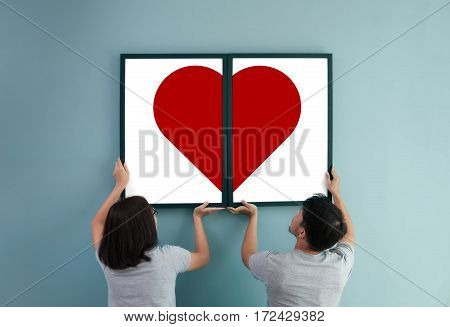 Valentine's day concept. Asian couple holding red heart in picture frames. Rear view of lover.