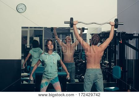 Muscular Man And Girl At Gym With Barbell And Dumbbells