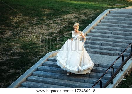 Pretty girl or cute bride with beautiful makeup and blond hair hairstyle in long white sexy wedding dress walking down grey stairs on sunny summer day outdoors on green grass background
