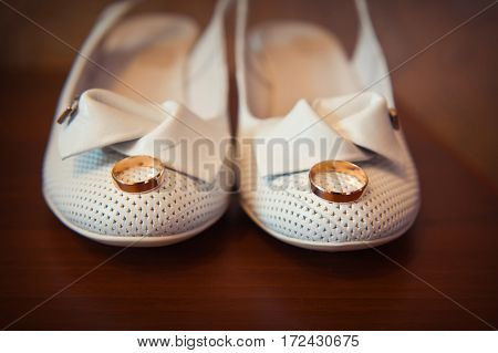 gold ring on the bride's white shoes closeup.