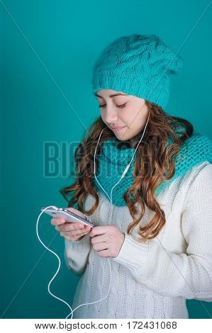 young woman with a phone in his hands listening to music on headphones.