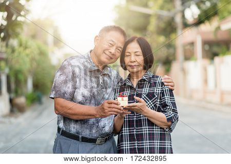 Happy senior Asian man give a gift box to senior Asian woman