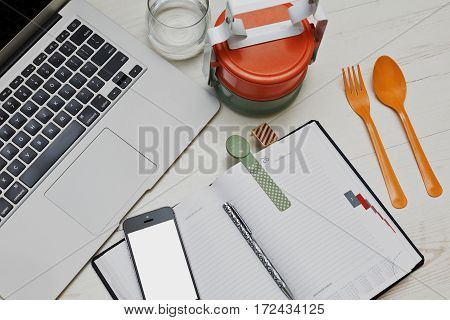 Fast lunch break in the office with colored asian styled food containers and typical business accessories - laptop cell and diary