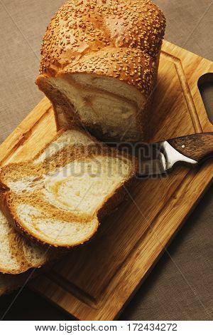 Unusual marble bread cutted on simple rural styled cutting board
