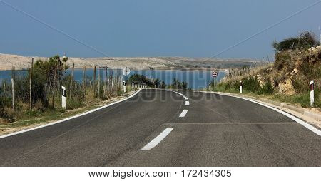 Road near the sea towards island.Asphalt road on sunny day on the seaside. Marked road on rocky southern  island.