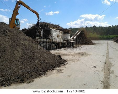 Green waste shredder and grapple handler in a sewage sludge composting plant