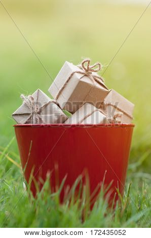 Gift boxes in red bucket on natural background Christmas and New Year concept. copy space.