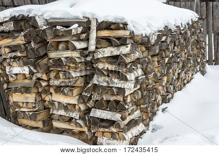 A large stack of birch wood covered with white snow.