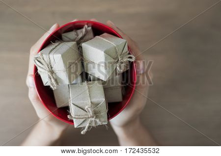 Hands holding gift boxes in red bucket on wooden background Christmas and New Year concept. copy space.