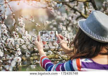 young woman in a hat takes on smartphone spring flowers on trees.