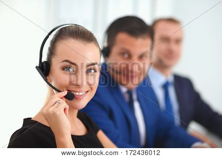 Portrait of beautiful business woman in headphones smiling with colleagues in background.