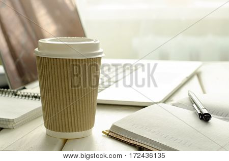 Paper cup of coffee on work-table with office stuff, notepad, laptop, pen and coffee cup, copy space, horizontal