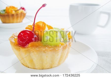 Appetizing cake basket with sliced fruit berries and cup of coffee on white background. Delicious and fresh dessert and coffee. Morning choice.