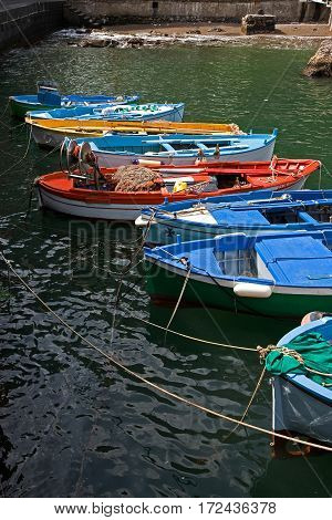 Colorful fishing boats tied up in the Amalfi harbor.