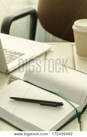 Open notepad with black pen on work-table. Paper cup of coffee, office stuff, laptop, copy space, vertical