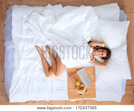 Young beautiful woman lying in bed at home.