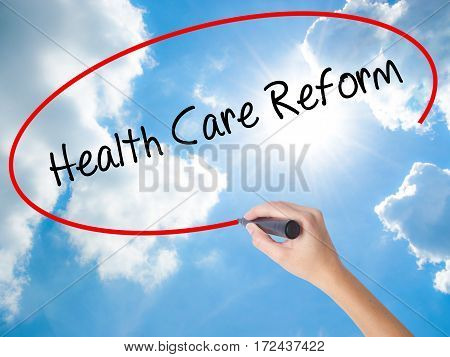 Woman Hand Writing Health Care Reform With Black Marker On Visual Screen